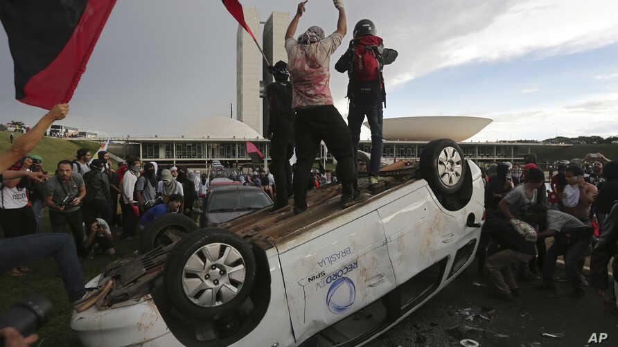 Protesters stand on an overturned car outside Congress where senators planned to vote on a spending cap bill and the lower Chamber of Deputies was considering controversial anti-corruption legislation, in Brasilia, Brazil, Tuesday, Nov. 29, 2016.