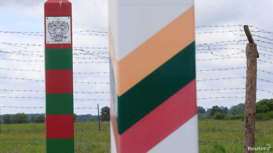 FILE - Lithuanian, right, and Russian border signs are seen near the Sudargas border crossing point with Russia in Ramoniskiai, Lithuania, June 5, 2017.
