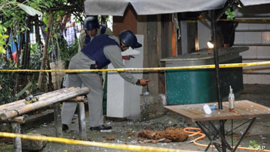 Police bomb personnel inspect the site where a book containing a bomb exploded while police were inspecting the package at the office of a moderate Islamic group in Jakarta, March 15, 2011