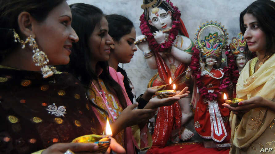 Pakistani Hindu women hold earthen oil lamps on the occasion of Diwali, in Lahore, on October 26, 2011. During Diwali, the festival of lights, people honour the Hindu goddess of wealth, Lakshmi, decorate their homes with flowers and diyas (earthen la