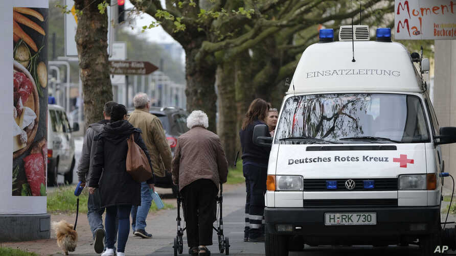 Inhabitants pass by rescue workers in Hannover-Vahrenfeld, northern Germany, May 7, 2017 when 50,000 people have to leave their homes when an unexploded World War II bomb is defused.