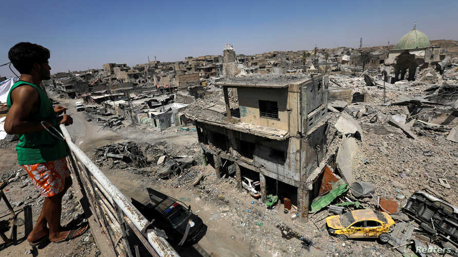 An Iraqi looks at the ruins of Grand al-Nuri Mosque and al-Hadba minaret in the destroyed Old City of Mosul, Iraq, Aug. 5, 2017.