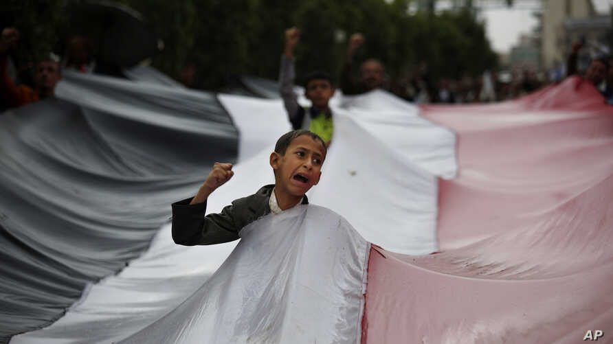 A boy chants slogans through a gap in a national flag raised by Shiite rebels, known as Houthis, during a protest against Saudi-led airstrikes in Sanaa, Yemen, April 15, 2016.