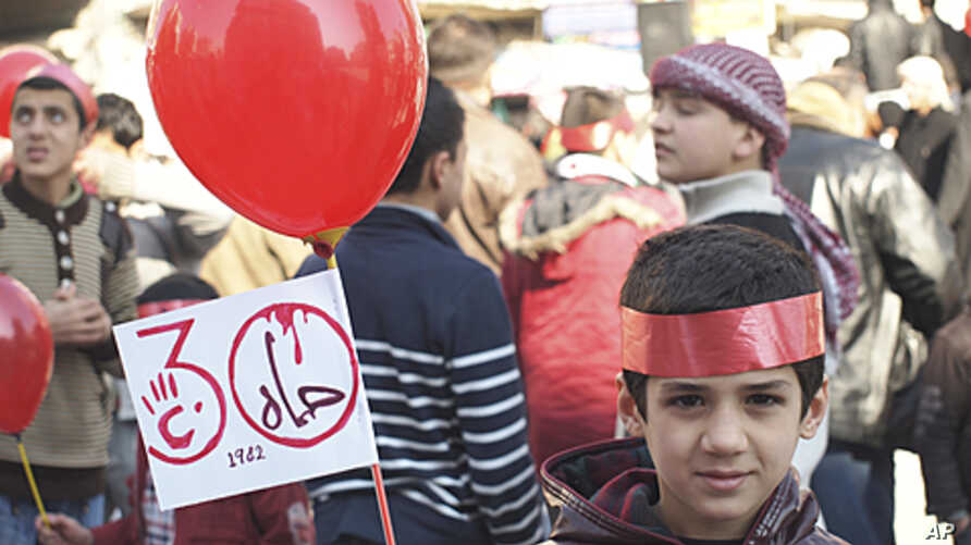 """A young boy holds up a sign that reads, """"Hama 1982,"""" during a protest against Syria's President Bashar al-Assad after Friday prayers in Idlib February 3, 2012."""