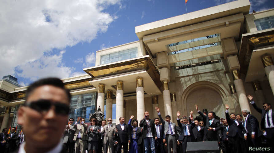 Mongolia's President Tsakhia Elbegdorj celebrates his re-election with members of his cabinet and party in front of the national parliament building in downtown Ulan Bator, June 27, 2013.