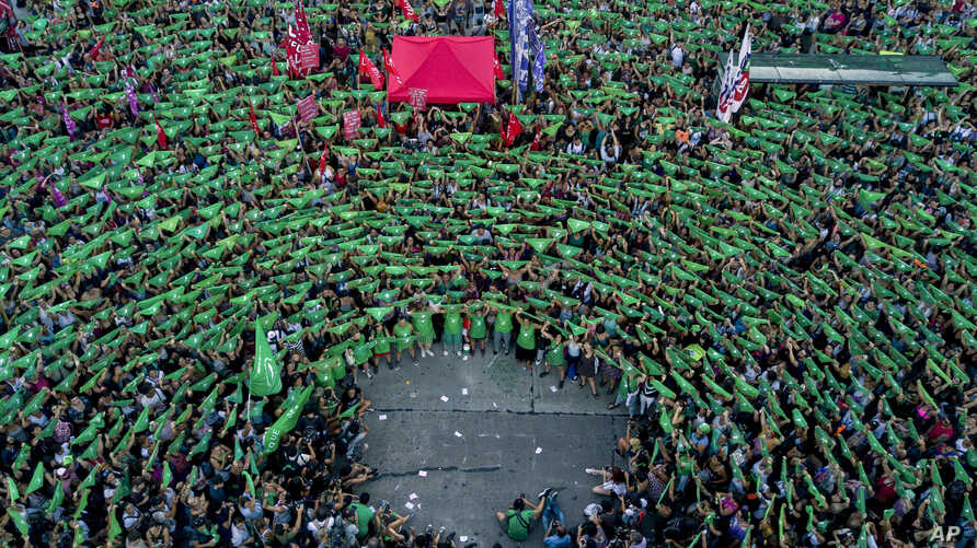 Pro-choice activists in favor of decriminalizing abortion raise green handkerchiefs as they rally outside Congress in Buenos Aires, Argentina, Tuesday, Feb. 19, 2019.