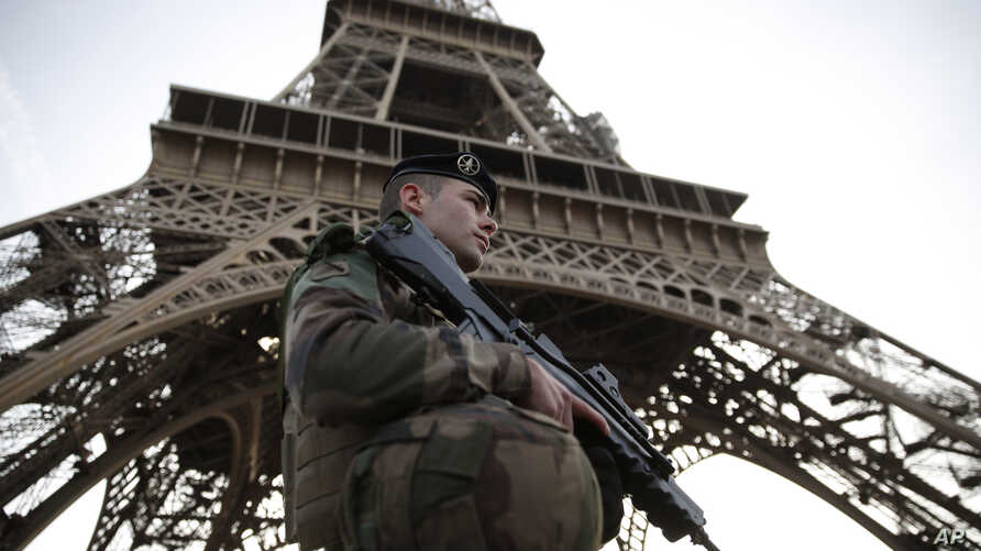 A French soldier stands guard under the Eiffel Tower in Paris, Nov. 1, 2017.