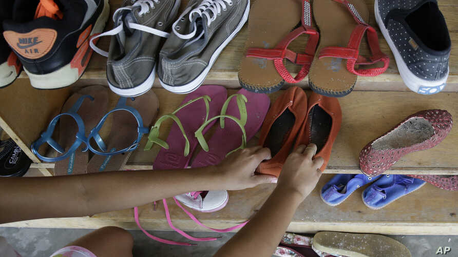A former cybersex victim arranges a shoe rack at a shelter for sexual exploitation survivors in Manila, Philippines, April 25, 2017.