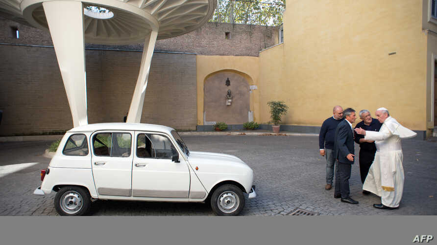This handout picture released by the Vatican Press Office shows Father Don Renzo Zocca (2ndR) offering his white Renault 4L to Pope Francis during a meeting at the Vatican, Sept. 7, 2013. (AFP photo/Osservatore Romano)