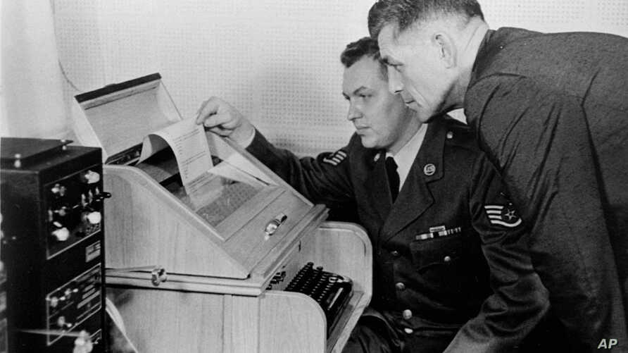 """This Aug.30, 1963 black-and-white file photo shows the White House Kremlin """"hot line"""" providing direct communication for emergency use by the Chief of Staff in Washington and Moscow, becaming operational. Air Force Sgt. John Bretoski, left, and Army"""