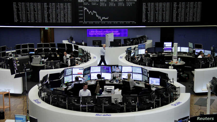 Traders work in front of the German share price index, DAX board, at the stock exchange in Frankfurt, Germany, May 18, 2017.
