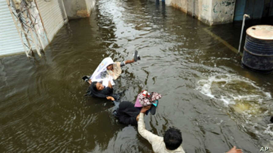 Pakistani men wade through floodwaters in Sujawal in southern Sindh province, Pakistan, 30 Aug 2010.  Floodwaters have begun to recede in the northwest and central parts of Pakistan.