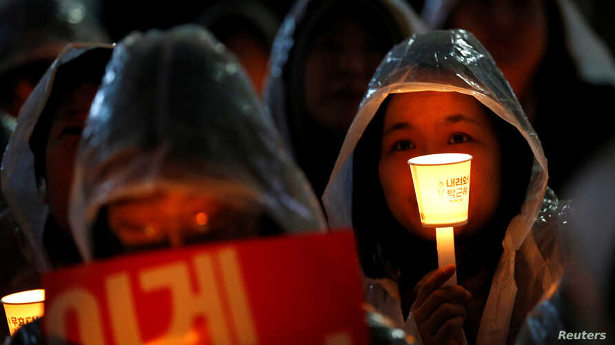 Protesters take part in a candlelight protest demanding South Korean President Park Geun-hye step down over a recent influence-peddling scandal, in central Seoul, South Korea, Nov. 18, 2016.