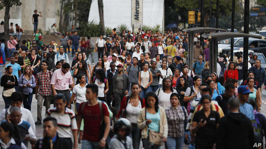 People spill out into an avenue after a power outage in Caracas, Venezuela, March 7, 2019. A power outage left much of Venezuela in the dark early Thursday evening.