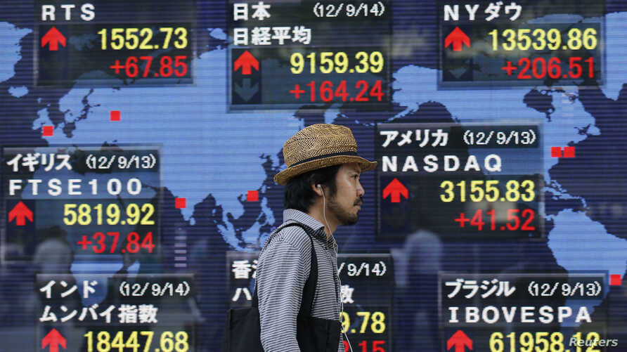 A man walks past a stock quotation board outside a brokerage in Tokyo, Japan, September 14, 2012.