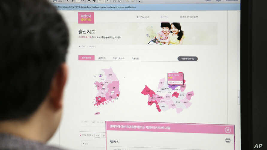 A journalist watches a screen showing a press release from the South Korean Ministry of the Interior about the birth map showing the number of women in childbearing age in Seoul, South Korea, Dec. 30, 2016.
