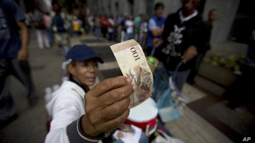 A street vendor inspects the authenticity of a 100-bolivar note as people stand in line outside a bank to deposit their 100-bolivar bank notes in Caracas, Venezuela, Tuesday, Dec. 13, 2016.
