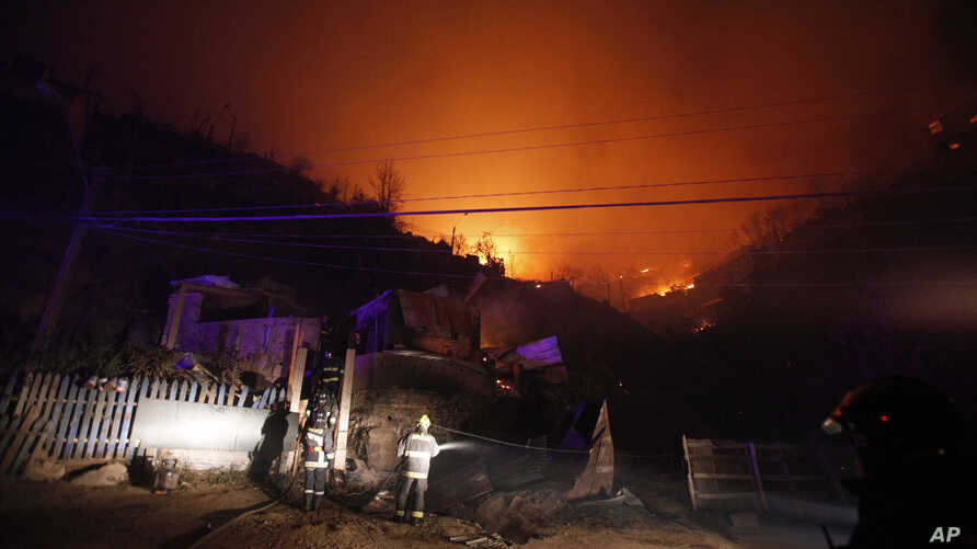 A group of firefighters stand next to destroyed homes as a forest fire rages towards urban areas in the city of Valparaiso, Chile, April 13, 2014.