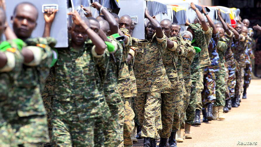 Uganda army soldiers at a military airbase in Entebbe carry the caskets containing the remains of Ugandan soldiers who were killed in Somalia this week, September 3, 2015.