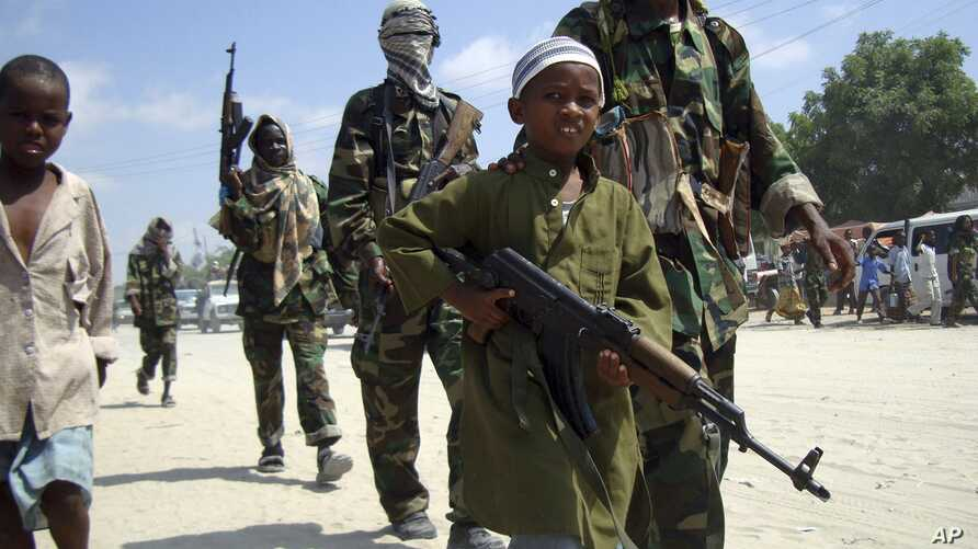 FILE - A young boy leads militant Islamist al-Shabab fighters as they conduct military exercises in northern Mogadishu's Suqaholaha neighborhood, Somalia, Jan. 1, 2010.