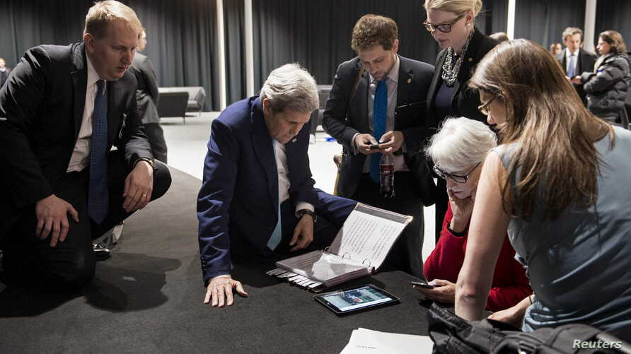 U.S. Secretary of State John Kerry (2nd L), U.S. Under Secretary for Political Affairs Wendy Sherman (2nd R) and staff watch a tablet in Lausanne as U.S. President Barack Obama makes a state address on the status of the Iran nuclear program talks, Ap