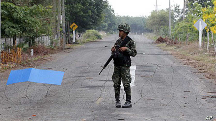 A Thai soldier mans a razor-wire roadblock close to the Thai-Cambodia border, shortly before cross-border fighting resumed for a third day, April 24, 2011
