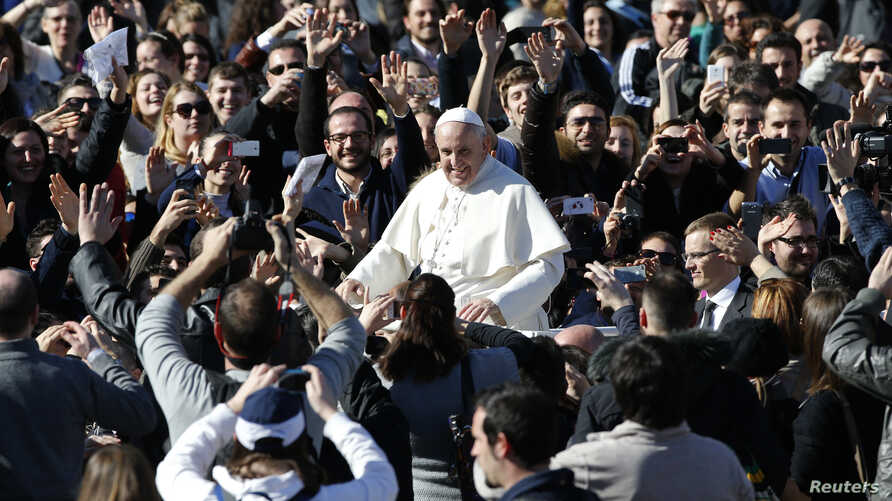 Pope Francis leaves at the end of a special audience with engaged couple, to celebrate Saint Valentine's day, in Saint Peter's square at the Vatican, Feb. 14, 2014.