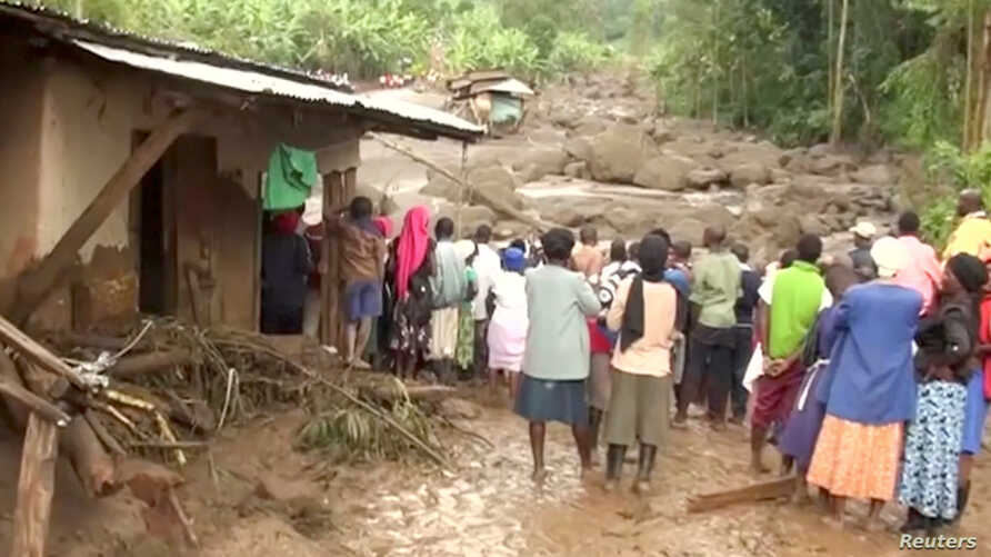 Residents watch flood waters pass through destroyed homes, after a landslide in Bududa, Uganda, in this still image taken from video, Oct. 12, 2018.