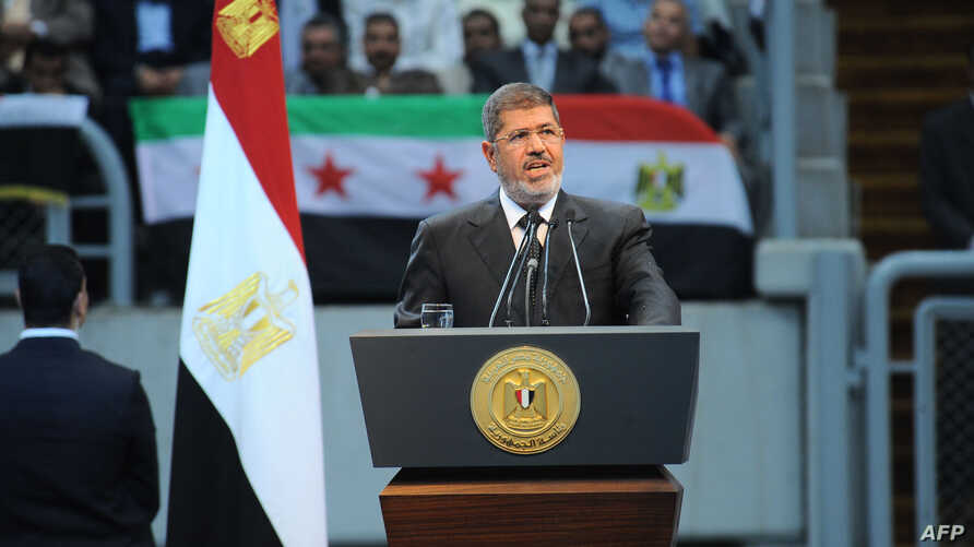 """In this handout picture Egyptian President Mohammed Morsi gives a speech to thousands of Islamists and Syrian opposition supporters during  the """"support for Syria"""" rally at Cairo stadium, June 15, 2013 in Cairo, Egypt. (Credit: Ho/Egyptian Presidency"""
