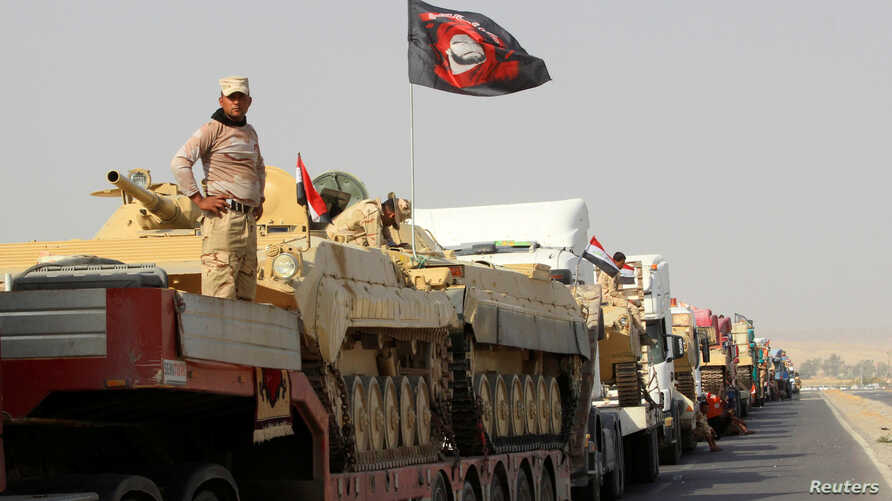 FILE - A convoy of Iraqi security forces advances on the outskirts of Mosul, Oct. 12, 2016. The battle for Mosul is weeks or perhaps days away.