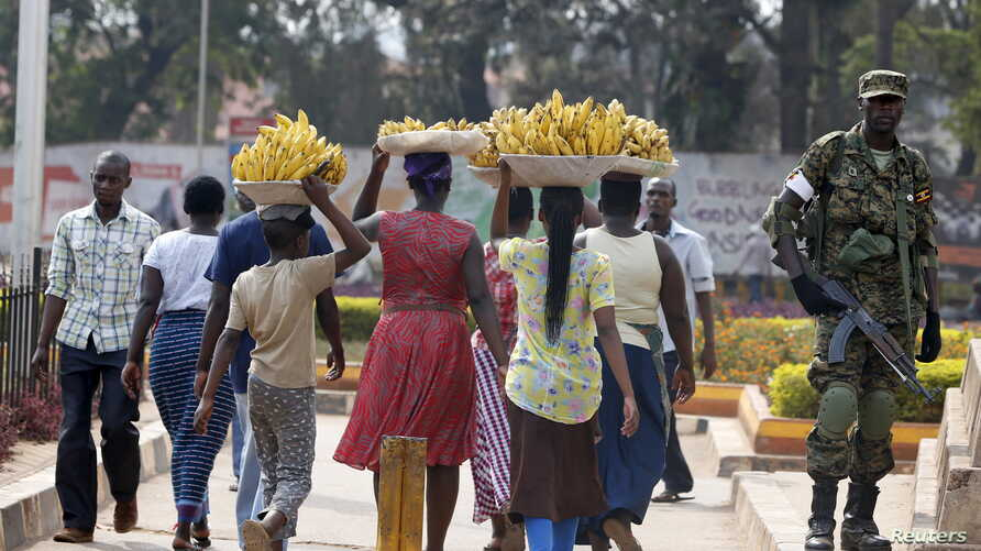 FILE - Women carry baskets of banana as they walk past a military personnel patrolling in Uganda's capital Kampala, February 19, 2016.