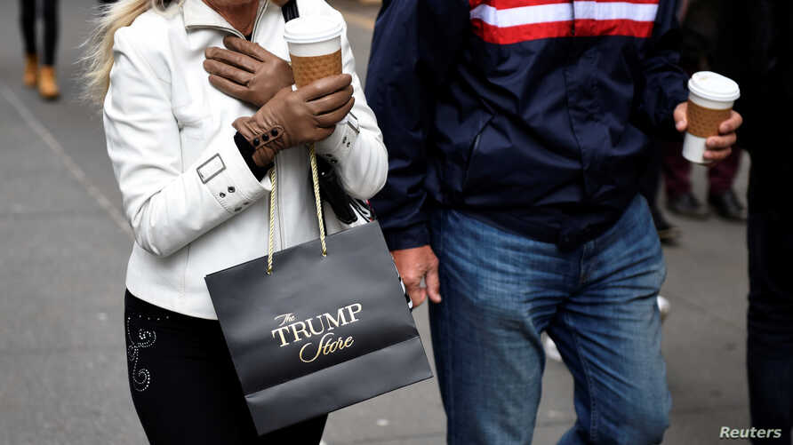 FILE - A woman carries a bag from The Trump Store after shopping at Trump Tower along Fifth Avenue in the Manhattan borough of New York, Nov. 20, 2016.