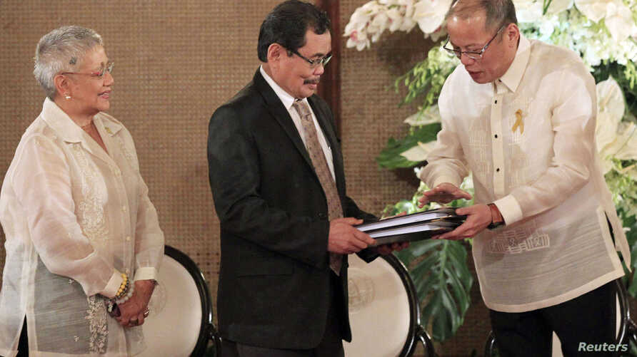 Philippine President Benigno Aquino hands over the draft Bangsamoro Basic Law (BBL) to Moro Islamic Liberation Front (MILF) chief negotiator Mohagher Iqbal (C) ahead of the turnover ceremony of the law at the presidential palace in Manila, September