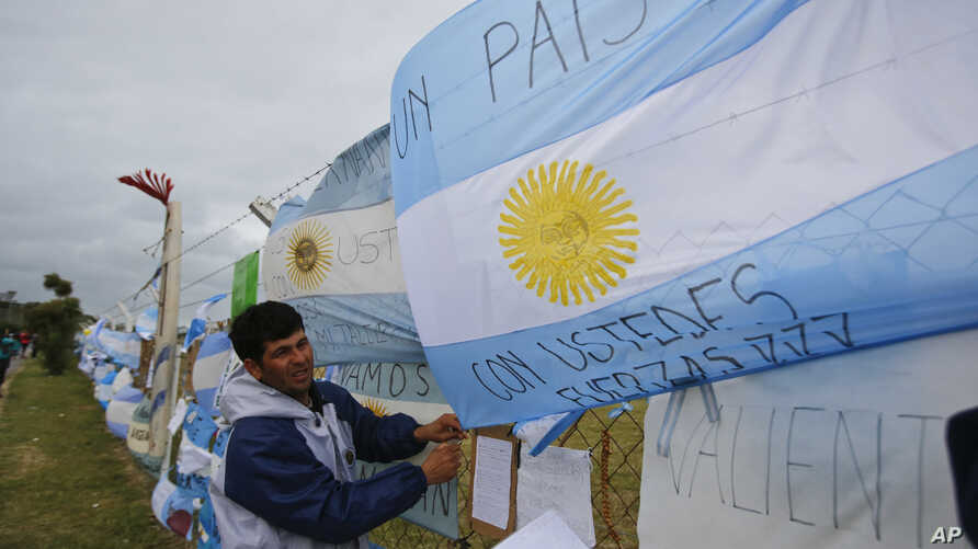 A man ties an Argentine flag carrying solidarity messages to a fence at the Mar de Plata Naval Base after the navy announced a sound detected during the search for the missing ARA San Juan submarine was consistent with that of an explosion, in Mar de
