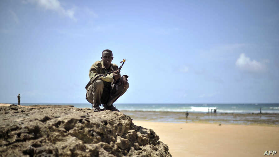 A handout picture released by the African Union-United Nations Information Support Team shows an armed man squatting at a beach during a demonstration by a local militia, formed in order to provide security in the town of Marka, April 30, 2014.