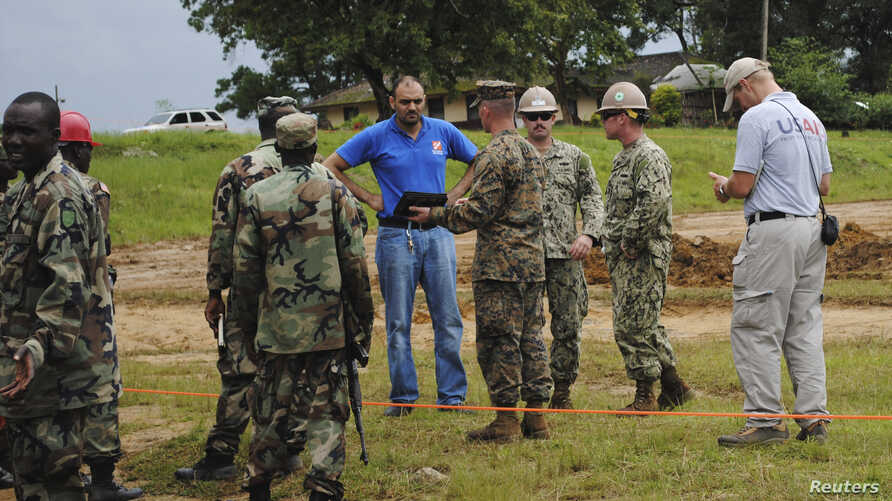 U.S. soldiers and their Liberian counterparts survey a construction site for an Ebola virus treatment center outside Monrovia on Oct. 3, 2014.