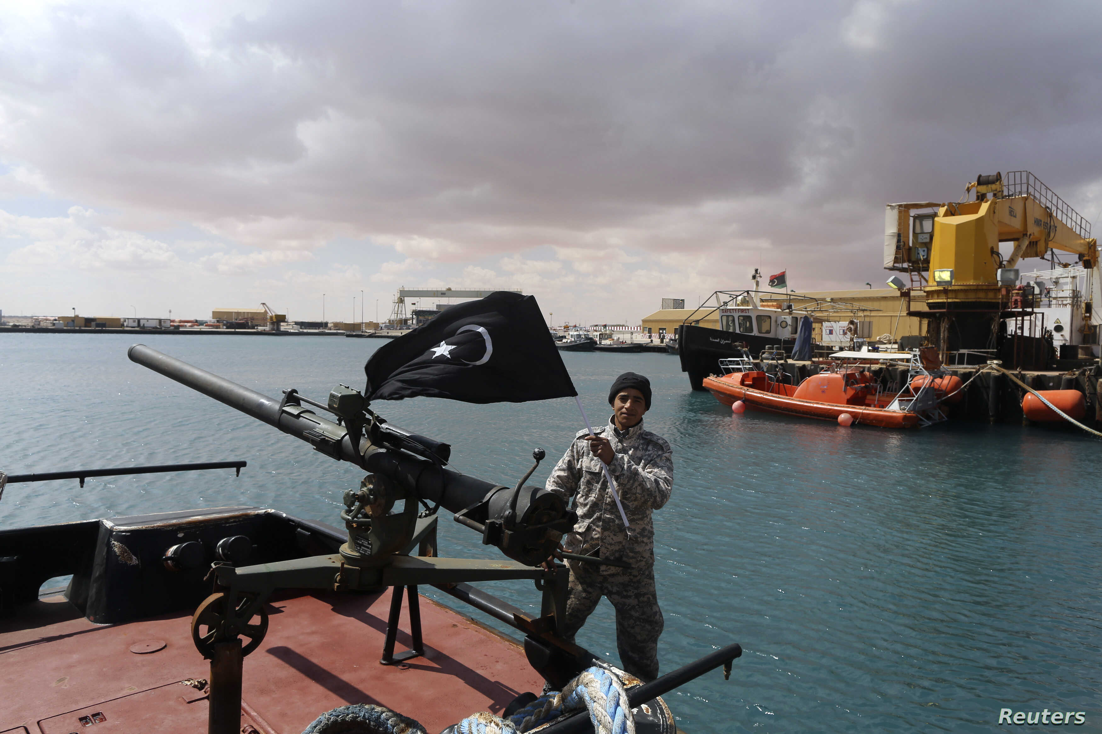 A rebel holds the Cyrenaica flag while standing on a boat where a North Korean-flagged tanker had loaded crude oil, at Es Sider port in Ras Lanuf, Libya, March 11, 2014.