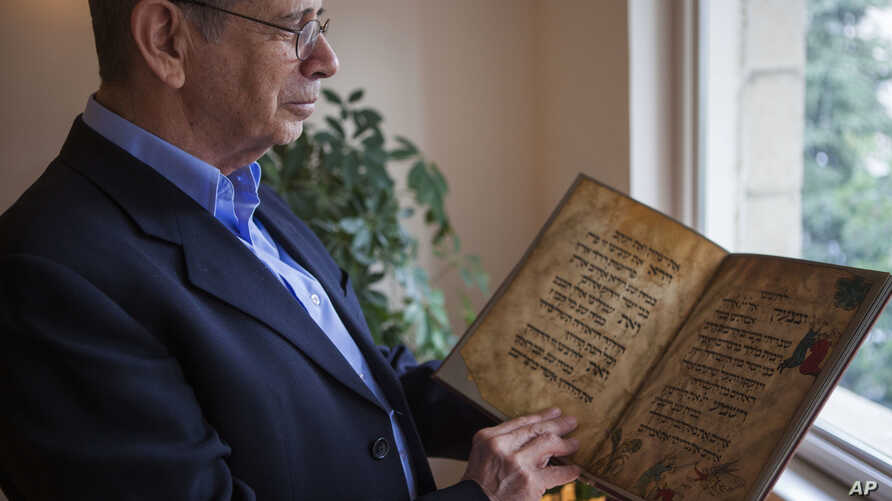 In this photo taken April 13, 2016, Eli Barzilai holds a copy of the Birds' Head Haggadah at his home in Jerusalem.