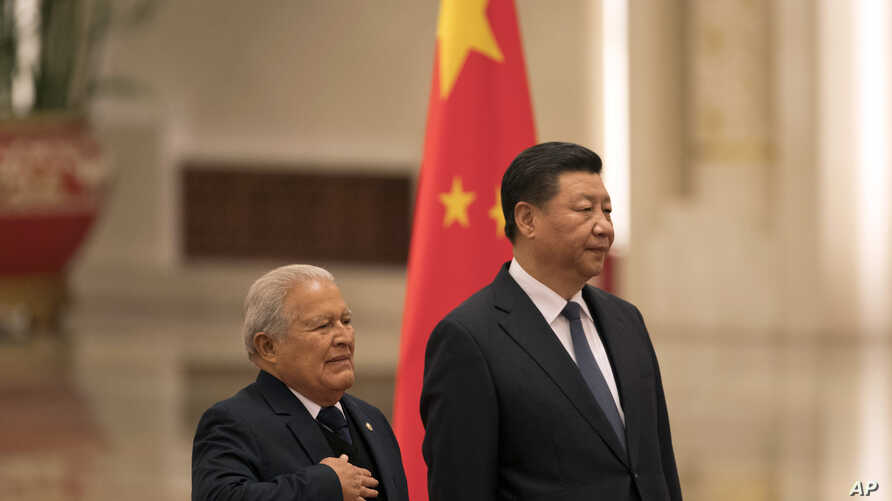 Salvadoran President Salvador Sanchez Ceren (L) standing next to Chinese President Xi Jinping, places his hand on his chest as the national anthem of El Salvador is played during a welcome ceremony held at the Great Hall of the People in Beijing, Nov