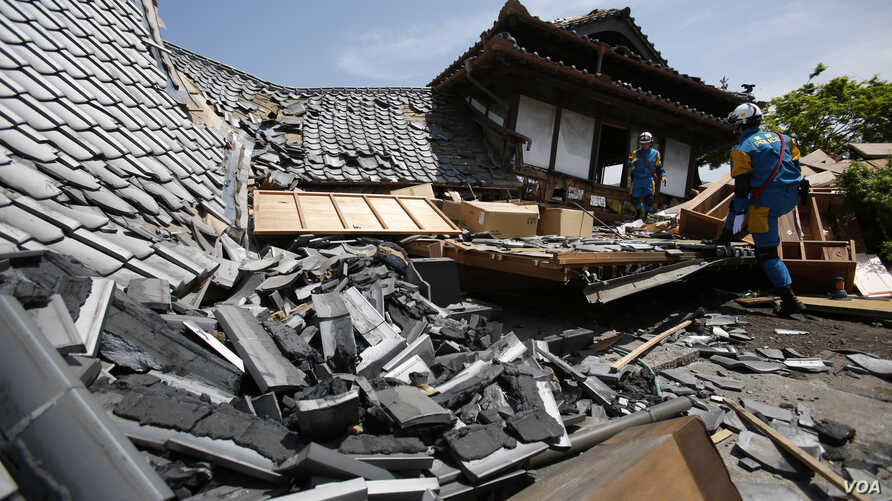 A rescue team searchs damaged houses for trapped people in Mashiki, Kumamoto prefecture, southern Japan, April 15, 2016.
