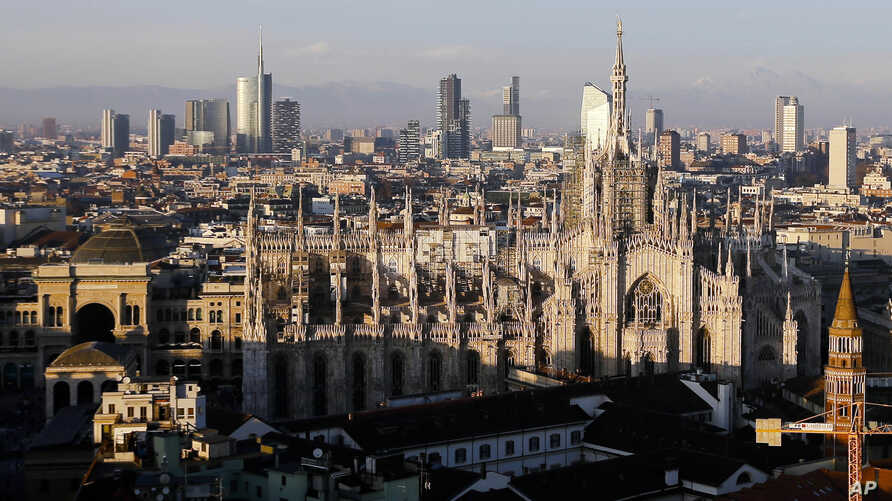 FILE - The pinnacles of the Duomo cathedral are lit by the afternoon sun and backdropped by the new Business Center, in Milan, northern Italy.