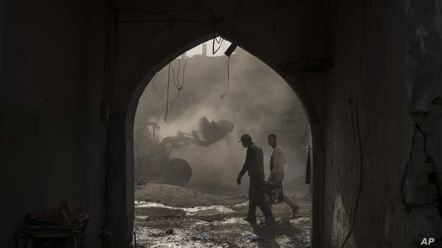 FILE - Construction workers carry a generator as a bulldozer remove debris from destroyed shops in the Old City of Mosul, Iraq, Nov. 18, 2017.
