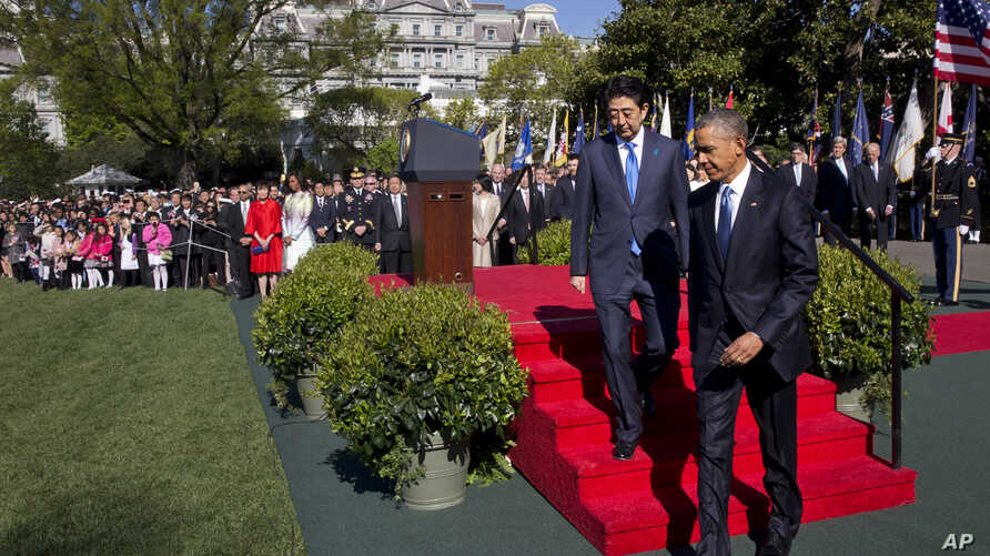President Barack Obama walks with Japanese Prime Minister Shinzo Abe during a state arrival ceremony, on the South Lawn of the White House in Washington, April 28, 2015.