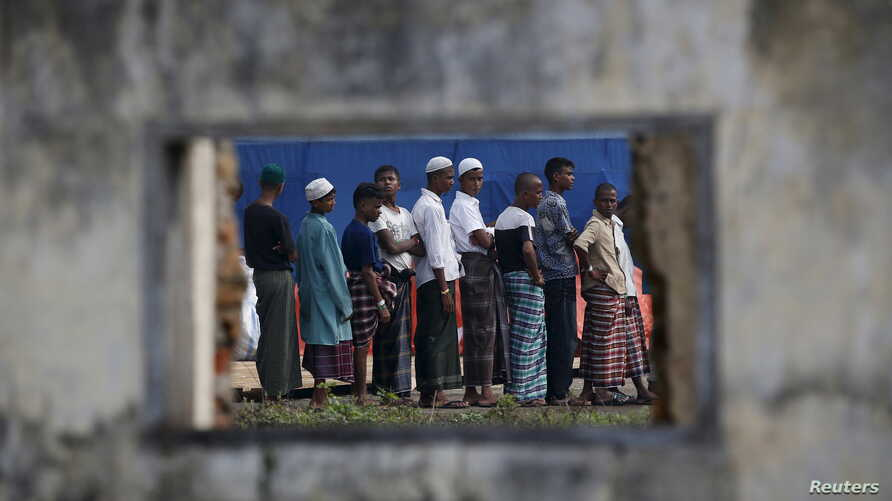Rohingya migrants who arrived in Indonesia last week by boat are seen through the window of an abandoned building as they wait in line for breakfast at a temporary shelter in Aceh Timur regency near Langsa in Indonesia's Aceh Province, May 27, 2015.