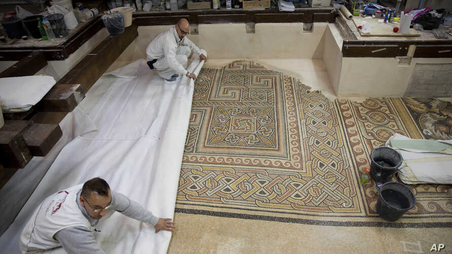 In this Dec. 6, 2018 photo, restoration experts work on a mosaic inside the Church of the Nativity, built atop the site where Christians believe Jesus Christ was born, in the West Bank City of Bethlehem.