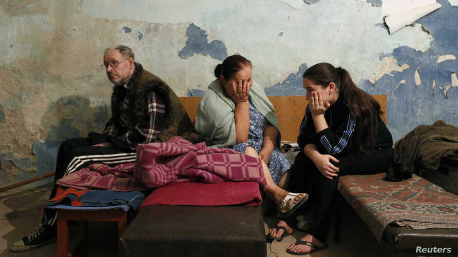 FILE - Local residents sit inside a bomb shelter where they are seeking refuge during what they say is shelling in Donetsk.