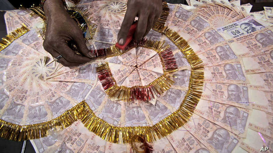 FILE - A shopkeeper prepares a garland with Indian 10 rupees denomination notes (USD $0.15) for sale, especially for wedding season, in Jammu, India, Friday, Nov. 11, 2016.