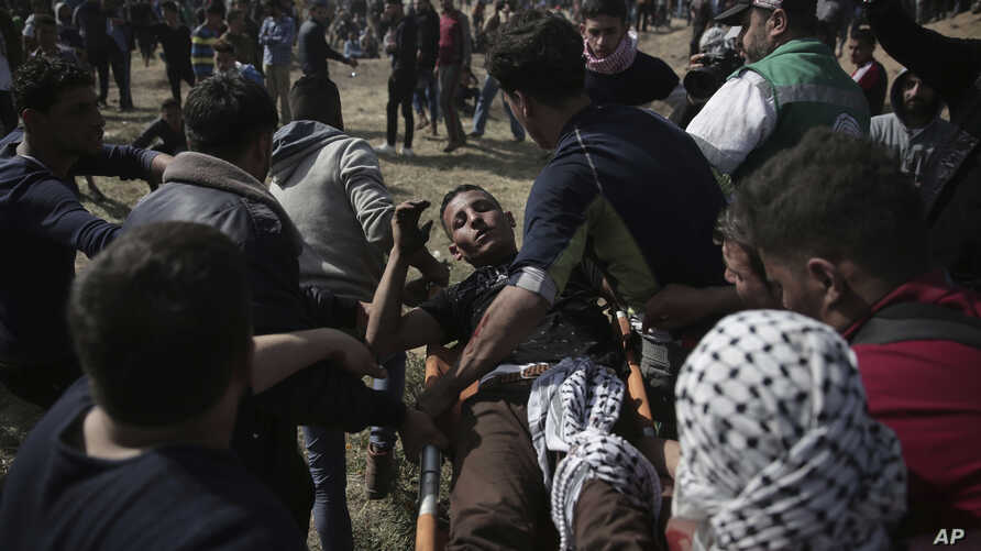 Palestinian protesters carry a wounded man from during a protest at the Gaza Strip's border with Israel, Friday, April 6, 2018.