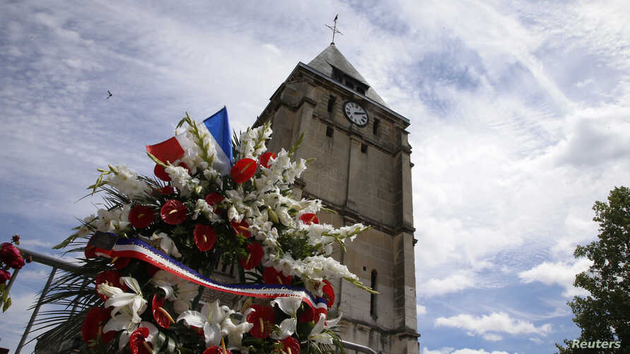 Flowers pay tribute to French priest Father Jacques Hamel outside the parish church at Saint-Etienne-du-Rouvray, near Rouen, France, July 28, 2016. Father Jacques Hamel was killed on Tuesday in an attack on the church that was carried out by assailan