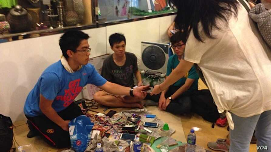 """Student volunteers offer a free phone charging service at """"Charging Corner"""" inside Hong Kong's occupied central business district. The students have adapted a multi-USB powerboard, and can charge up to 80 telephones from one electric socket, Oct. 8,"""
